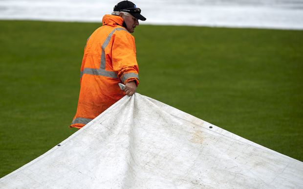 A groundsman pulls the covers as rain falls during a cricket game.