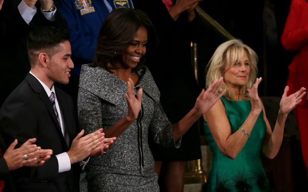 First lady Michelle Obama, alongside Dr Jill Biden (R), waves after arriving for US President Barack Obama's State of the Union speech.