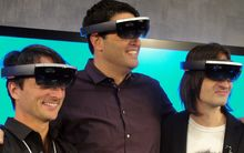 Microsoft executives Joe Belfiore, Terry Myerson and Alex Kipman pose wearing HoloLens eyewear that overlays 3D images on the real world.
