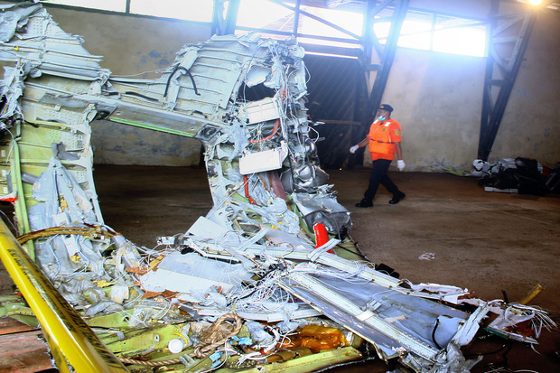 A member of Indonesia's search and rescue team walks past wreckage of AirAsia flight QZ8501 stored in a warehouse.