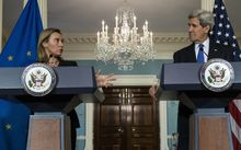 US Secretary of State John Kerry (R) listens while EU High Representative Federica Mogherini makes a statement to the press after a working lunch at the US Department of State in January 2015.