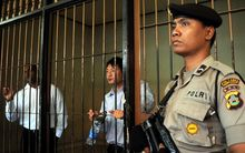 An Indonesian policeman stands guard next to a detention room where Australians Myuran Sukumaran (L) and Andrew Chan (C), members of the so called Bali Nine gang, wait for their trial.