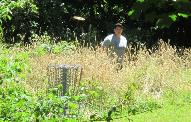 A competitor throws from the rough in the 2015 Rotorua Disc Golf Championships.