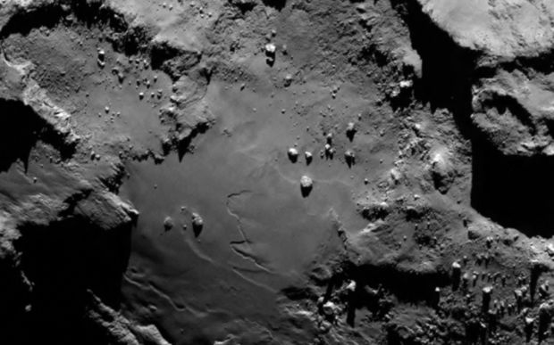 "A close-up photo showing the smooth region on the ""base"" of the ""body"" section of comet 67P."