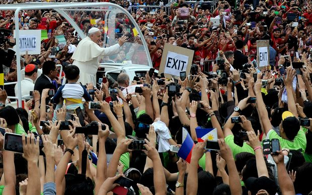 Pope Francis waves to crowds in Manila.