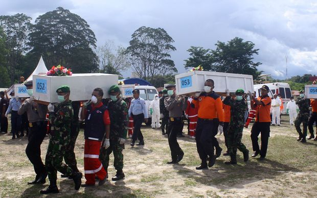 Indonesian rescue personnel load coffins bearing bodies recovered from the underwater wreckage of AirAsia flight QZ850.