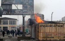 People look at a burning shop after shelling in the southern Ukrainian port city of Mariupol.
