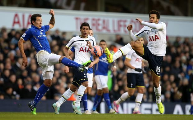 Leonardo Ulloa of Leicester City tangles with Mousa Dembele of Tottenham Hotspur