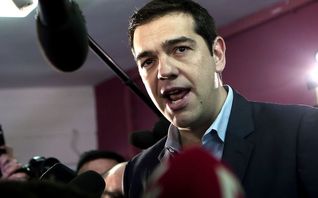The leader of Greece's left-wing Syriza party Alexis Tsipras (C) talks to journalists after voting at a polling station in Athens in January 2015.