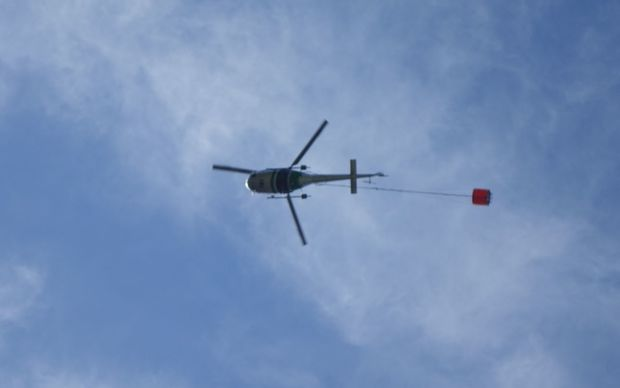 A helicopter with a monsoon bucket fights a fire at Arthur's Pass.