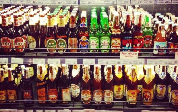 A supermarket shelf stocked with bottles of imported beer.