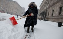 A library employee works to clear the sidewalks in front of the main branch of the Boston Public Library during a blizzard on 27 January 2015 in Boston, Massachusetts.