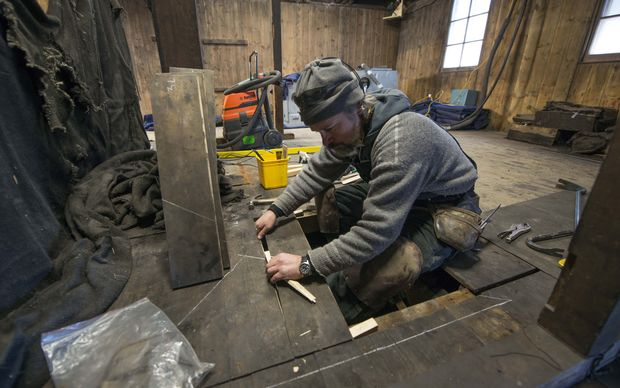 Lead carpenter Gordon Macdonald lifts the floorboards at Scott's Discovery Hut.