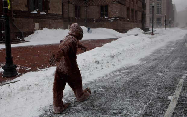 A pedestrian dressed as Bigfoot makes their way through the strong wind and snow in Boston.