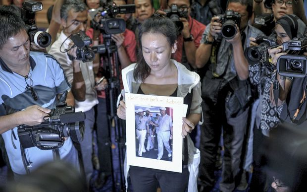 "A relative of a passenger of flight MH370 holds a picture of Malaysian Prime Minister Najib Razak with the words ""please bring back my husband""."