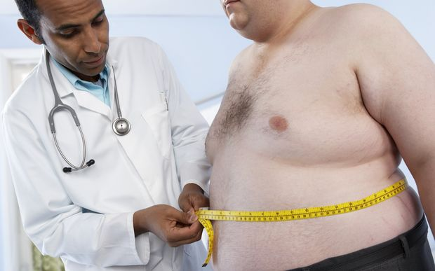 Doctor measuring the waist of an obese patient.