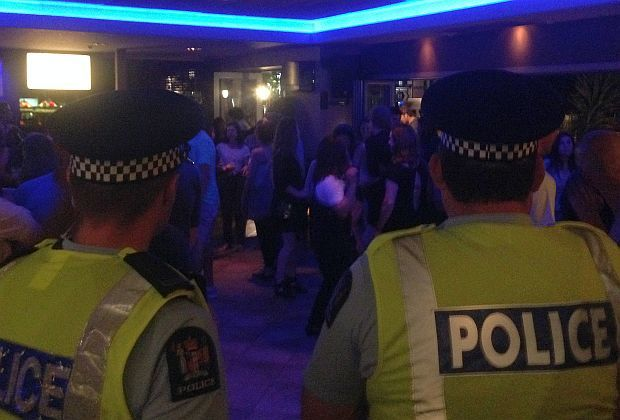 Two police officers in uniform look on as clients dance at night in bar