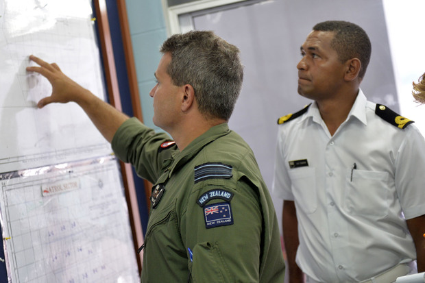 Squadron leader Dale Harlos details the patrol area with Apakuki Tukana of Fiji's Navy.