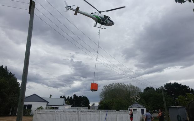 A helicopter fills monsoon bucket from a swimming pool.