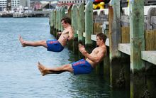 Sam Dickson, left, and Scott Curry synchronise dive into Wellington Harbor after training.