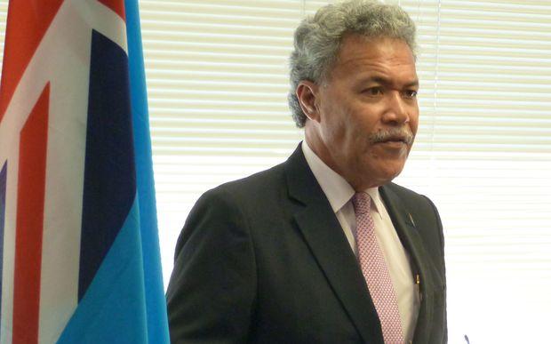 Tuvalu Prime Minister Enele Sopoaga and the flag of Tuvalu.
