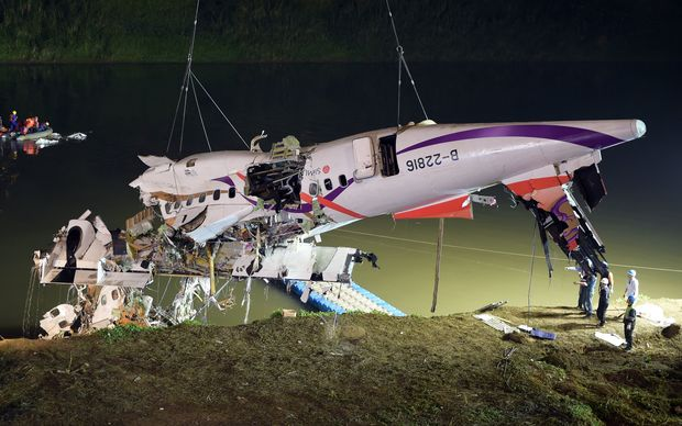 Rescuers lift the wreckage of the TransAsia ATR 72-600 out of the Keelung river at New Taipei City on February 4, 2015.