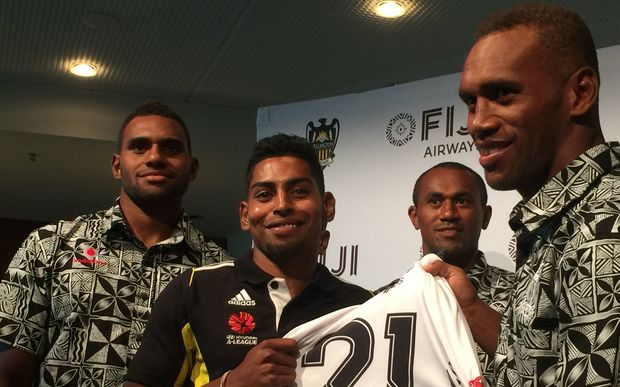 Wellington Phoenix striker Roy Krishna is presented with a jersey by the Fiji rugby sevens team.