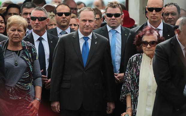 John Key is escorted onto Te Tii Marae at Waitangi by Ngapuhi kuia Titewhai Harawira (R) and Ngati Whatua leader Naida Glavish.
