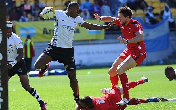 Fiji's Vatemo Ravouvou fends off tackles to score a try against Wales on Day 1 of the IRB Sevens Series Rugby Tournament in Wellington, 2015.