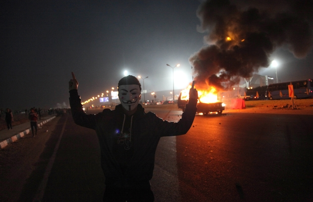 A man gestures near a burning car during clashes between Zamalek football club supporters and security forces on 8 February 2015.