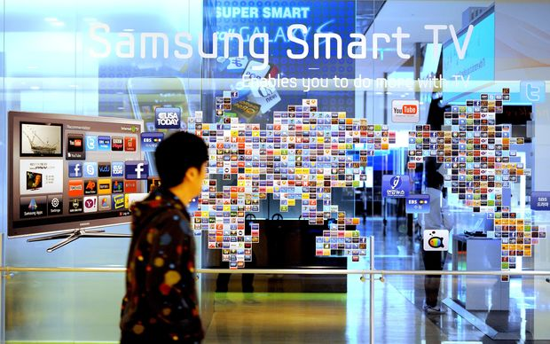 A man walks past a Samsung smart TV advertisment at a showroom in Seoul, South Korea, in 2011.
