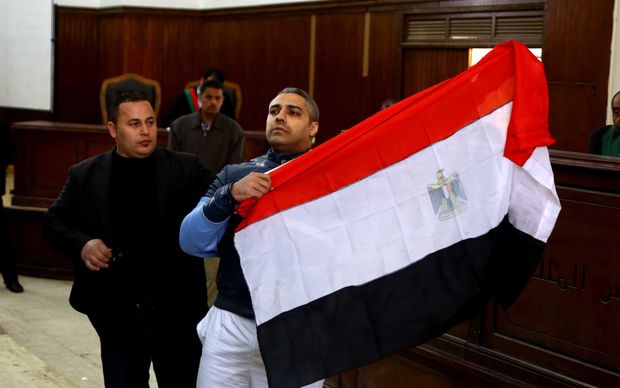 Mohamed Fahmy unfurls Egyptian flag during the hearing.