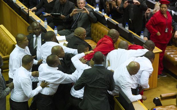 Members of the Economic Freedom Fighters, wearing red uniforms, clash with security forces during South African President's State of the Nation address.