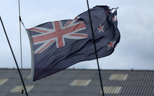Tattered New Zealand flag flying high on a yacht in Wellington.