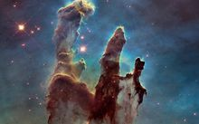 The Eagle Nebula's Pillars of Creation - gas clouds and dust shaped by nearby stars.