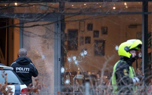 Policemen secure the area around a building in Copenhagen where shots were fired.
