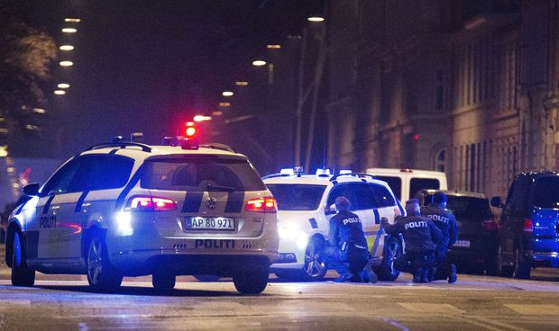Police officers take cover behind their patrol cars after one person was shot in the head and two policemen were shot in the arm and leg in Krystalgade.