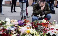 "A man reacts next to flowers for the shooting victims outside the ""Kruttoende"" cultural centre in Copenhagen."