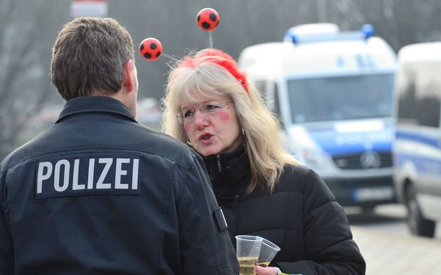 A Police officer speaks with a carnival reveler in Braunschweig.