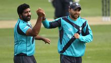 Majid Haq of Scotland celebrates with Preston Mommsen after taking a wicket.