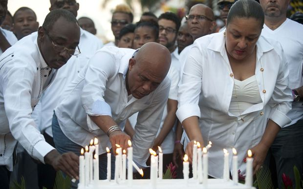 Haitian President Michel Martelly (C) places a candle with First Lady Sophia Martelly (R), and Prime Minister of Haiti, Evans Paul (L), at the site of an accident during the march convened by the government in Port-au-Prince on February 17, 2015