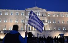 A man holds a Greek flag in front of the Greek parliament in Athens as people gather in support to their government.