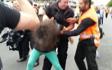 A woman protesting at Auckland's Pride Parade is handled by security guards.