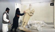 An image grab taken off a video by Islamic State allegedly shows a militant pushing a statue inside the Mosul museum.