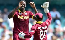 West Indies paceman Jason Holder (L) celebrates his wicket of South Africa's batsman Quinton de Kock (not pictured) with a teammate Denesh Ramdin during the Pool B 2015 Cricket World Cup match between South Africa and West Indies at the Sydney Cricket Ground on February 27, 2015.