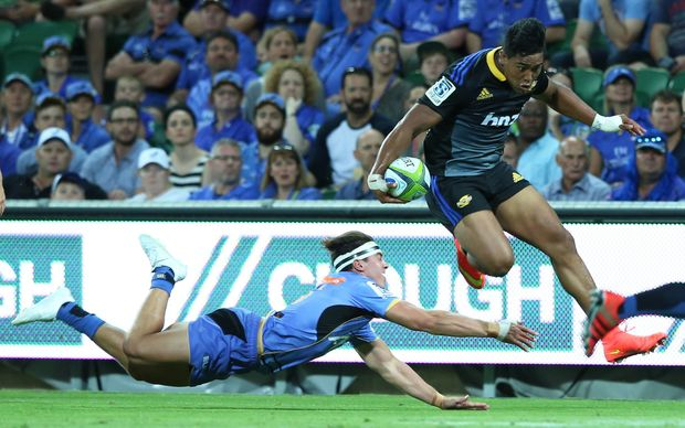 Hurricanes star Julian Savea hurdles a Force defender
