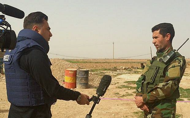 Imran Khan wearing flak jacket holds mic out as he interview Iraqi officer