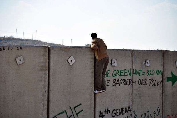 Young man man climbs concrete separation wall