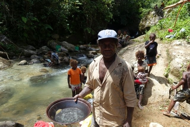 A man from Nusuta village showing the gold produced from two to three hours work at the Charivunga river near pit 4, also known as Dawsons. He estimates that there are seven to eight grams of gold in his pan. He produced this with the help of his wife and children.