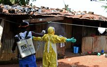 A health worker from Sierra Leone's Red Cross is sprayed with disinfectant in Freetown in November 2014 (file photo).